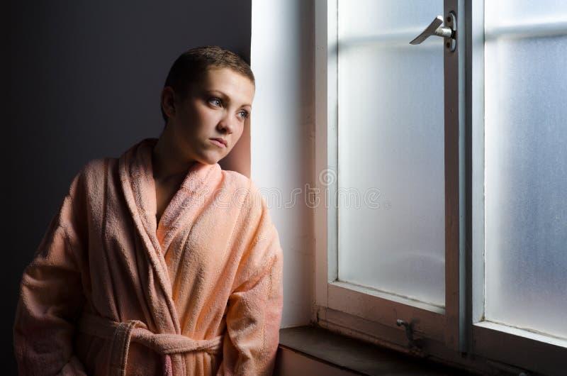 Enfermo de cáncer joven que se coloca delante de ventana del hospital imagen de archivo