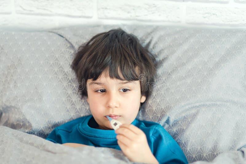 Enfermo de la gripe del niño, muchacho con el termómetro médico en la boca, enfermedad de la salud El ni?o con rinitis fr?a, se e imagen de archivo libre de regalías