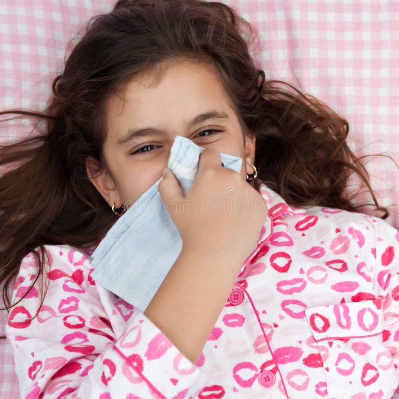 Enfermo de la muchacha de Hspanic con la gripe y el estornudo imagenes de archivo