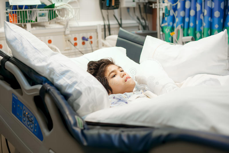 Enfermo de mentira del niño pequeño discapacitado en cama de hospital imagen de archivo