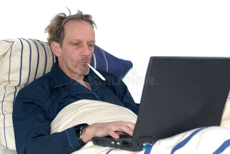 Enfermo en cama con la computadora portátil. fotografía de archivo libre de regalías
