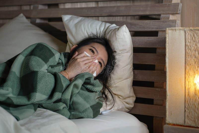 Enfermo hermoso joven y frío sufridor agotado y gripe de la mujer japonesa asiática que tienen temperatura que miente en la cubie fotografía de archivo libre de regalías