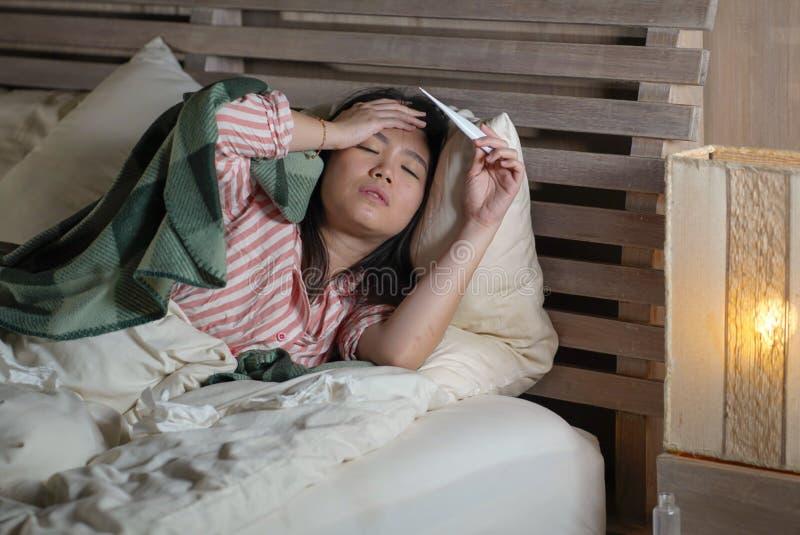 Enfermo hermoso joven y termómetro sufridor agotado de la tenencia del frío y de la gripe de la mujer china asiática que tienen t fotos de archivo