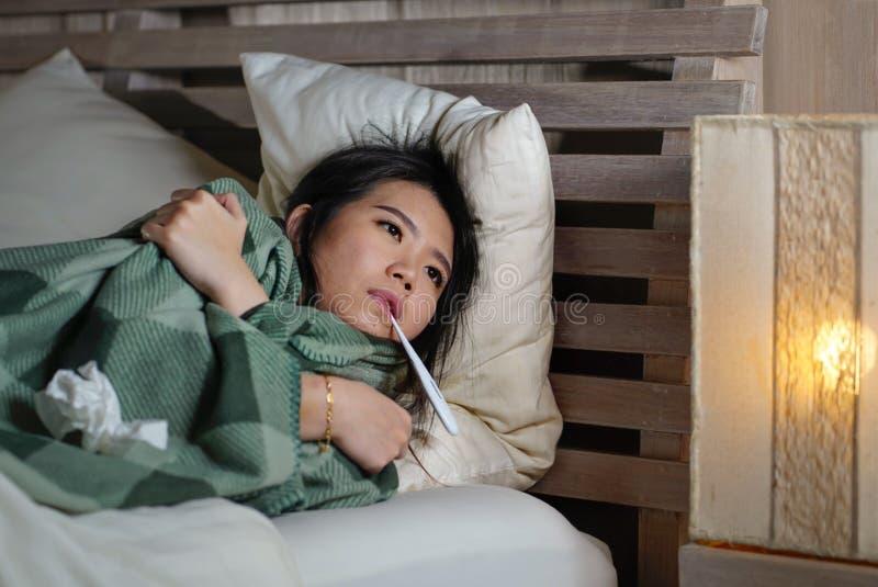 Enfermo hermoso joven y termómetro sufridor agotado de la tenencia del frío y de la gripe de la mujer coreana asiática que tienen fotografía de archivo