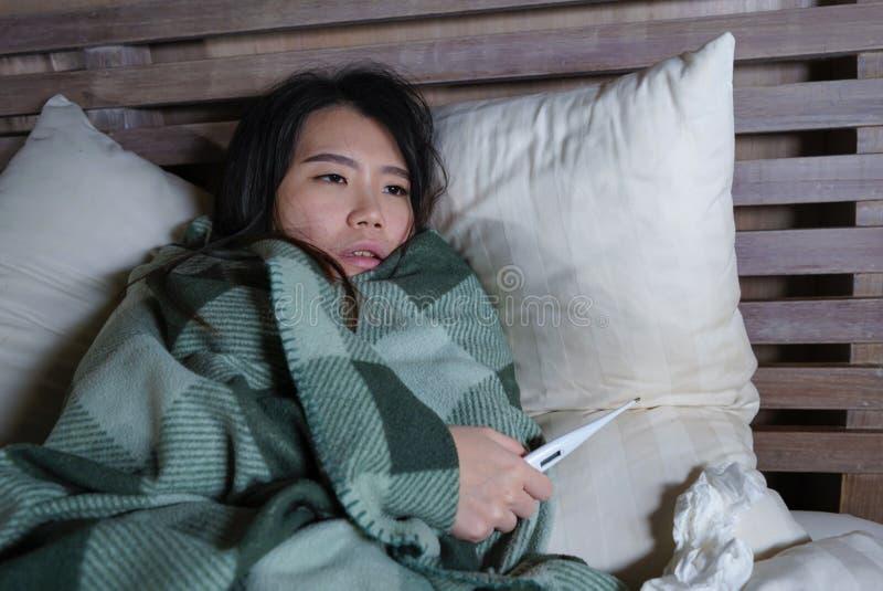 Enfermo hermoso joven y termómetro sufridor agotado de la tenencia del frío y de la gripe de la mujer japonesa asiática que tiene fotos de archivo libres de regalías