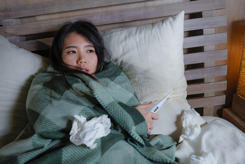 Enfermo hermoso joven y termómetro sufridor agotado de la tenencia del frío y de la gripe de la mujer japonesa asiática que tiene imagen de archivo libre de regalías