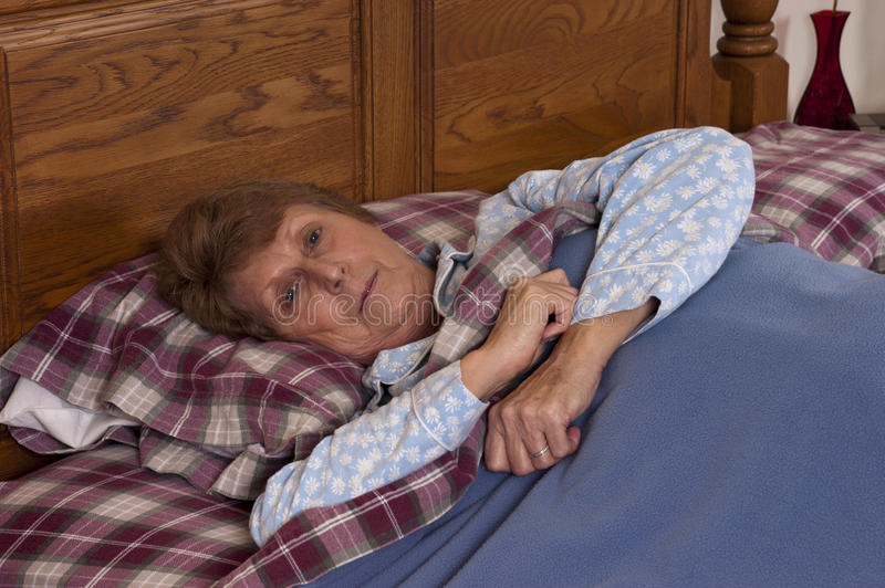Enfermo inválido de la mujer mayor madura en cama fotos de archivo libres de regalías
