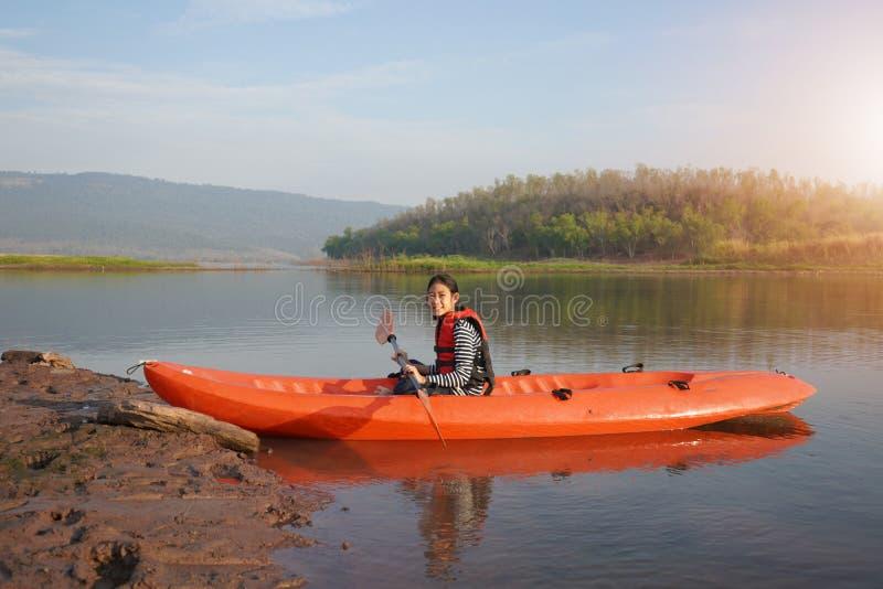 Enfileiramento da menina uma canoa em águas calmas imagens de stock royalty free