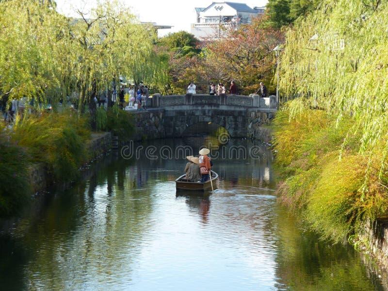 Enfileirando um barco dos turistas ao longo da área do canal de Kurashiki, Japão fotografia de stock royalty free