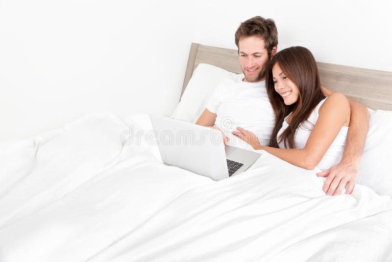 Enfoncez les couples heureux sur l'ordinateur portable dans la chambre de lit photos stock