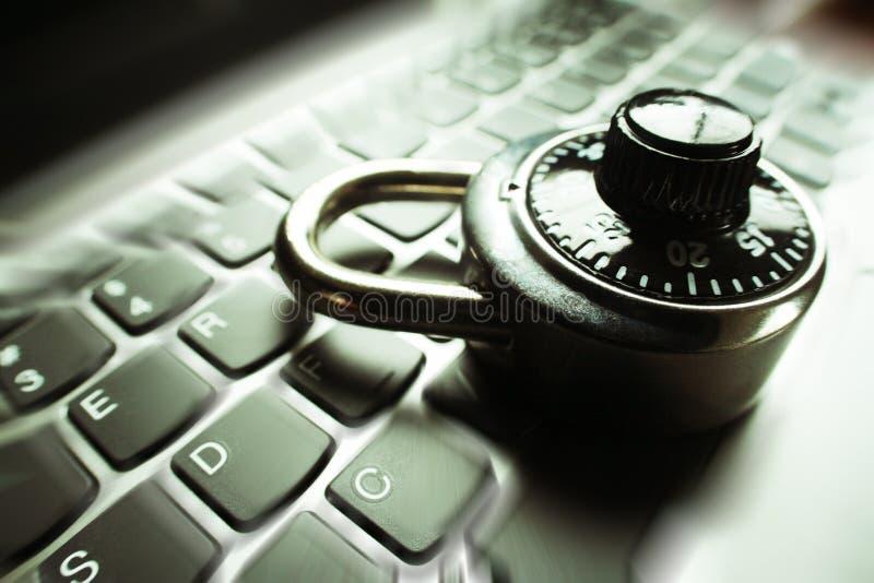 Enfoque negro de la cerradura de combinación estallado en el teclado del ordenador portátil que representa seguridad cibernética imagenes de archivo