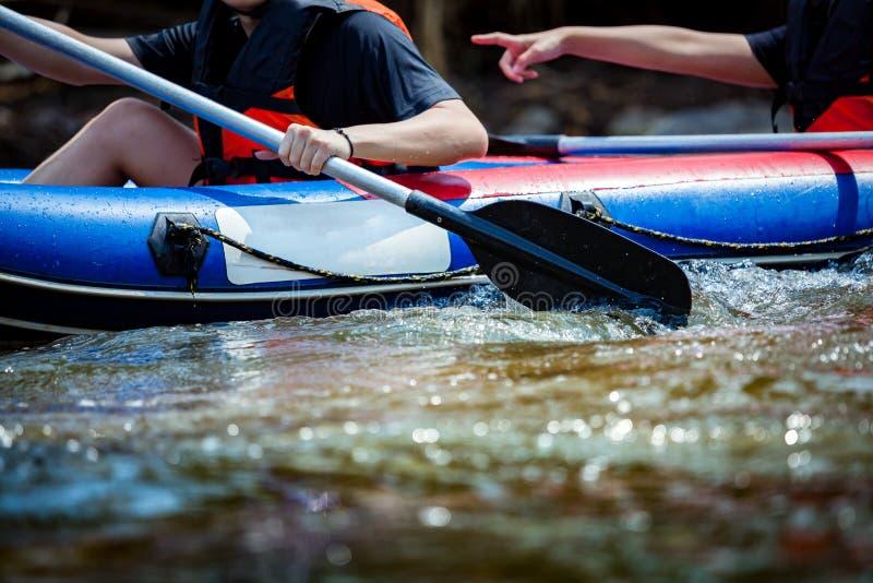 Enfoque a una cierta parte de la persona joven están transportando en balsa en el río fotografía de archivo libre de regalías