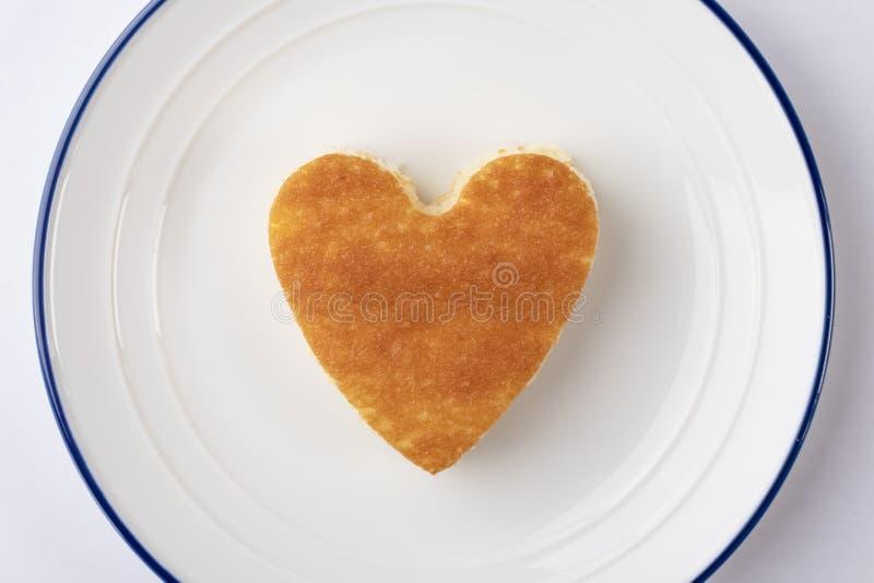 Enformad muffin på en vit platta med en blå gräns royaltyfri bild