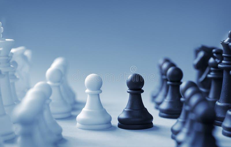 Enfrentamiento de pedazos de ajedrez blancos y negros en un fondo azul claro foto de archivo