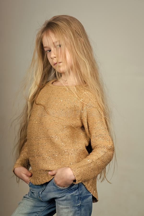 Enfrente a menina ou a criança da forma em sua site Forme a vestir da criança da menina calças de brim roupa sobre o fundo cinzen fotos de stock