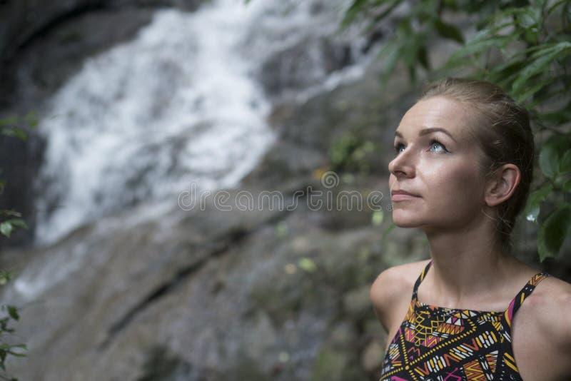 Enfrente o close up da mulher loura bonita que olha acima sobre a cachoeira borrada fotos de stock royalty free