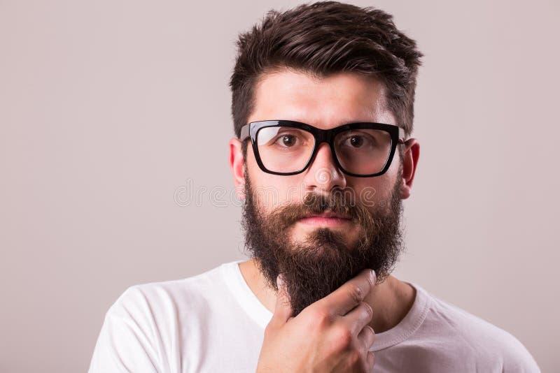 Enfrente o retrato do homem farpado nos vidros com mão na barba foto de stock royalty free