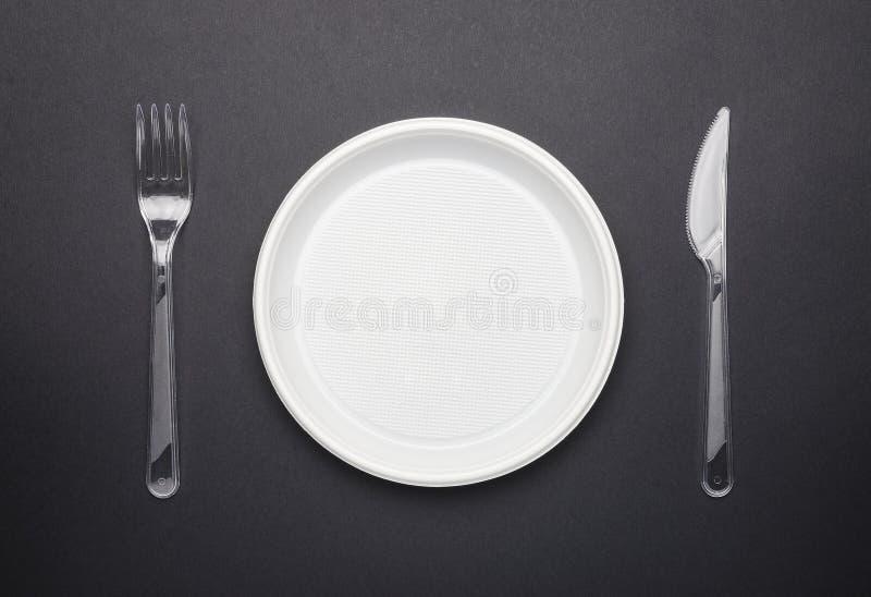 eng?ngsplastic bordsservis Platta, gaffel och kniv p? svart bakgrund fotografering för bildbyråer
