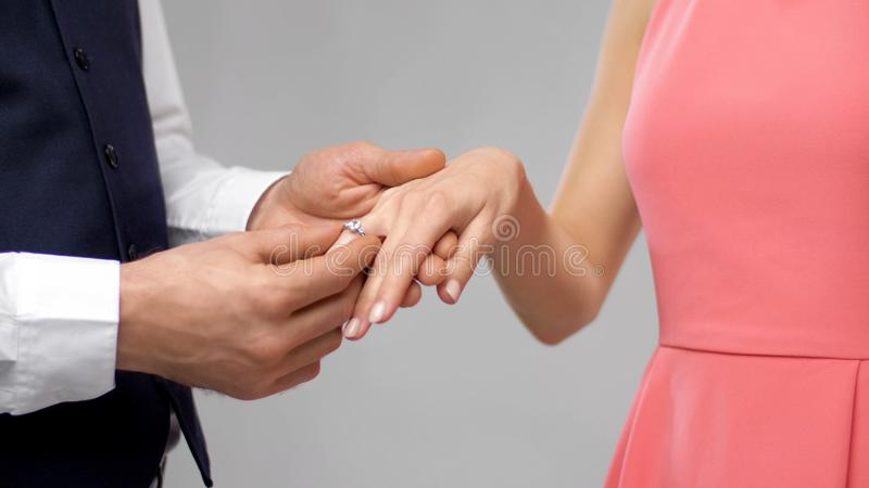 Man puts engagement ring on womans finger stock image