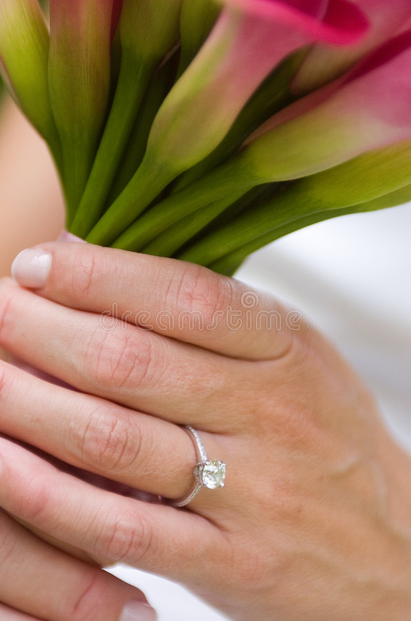 Engagement ring. Bride holding flowers with ring showing royalty free stock images