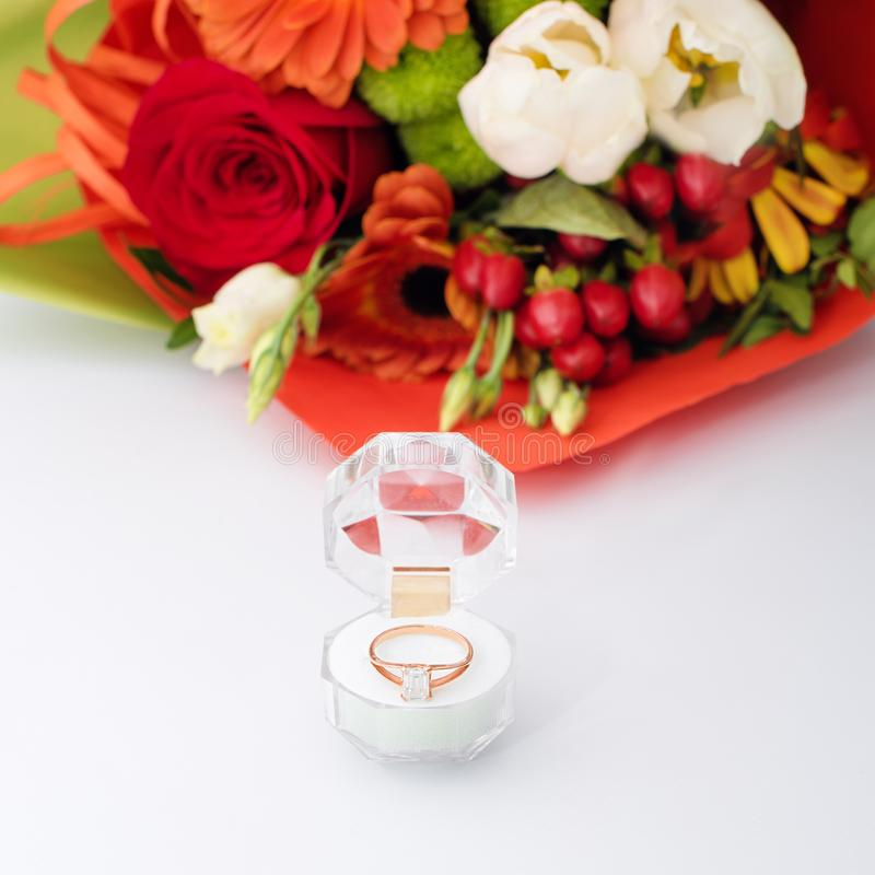 Engagement Ring In A Gift Box With Bright Bouquet Of Flowers. The ...