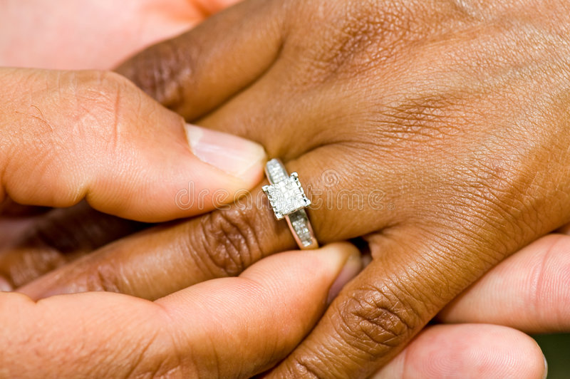 Engagement ring and hands. A view of the hands of an African-American man and woman with the focus on a beautiful diamond engagement ring just given to the woman royalty free stock photography