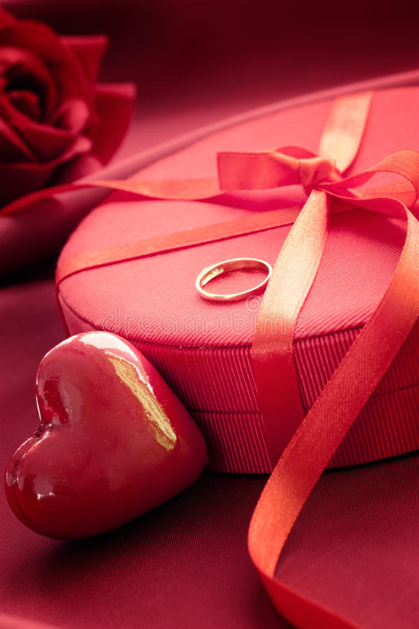 Engagement ring on present. Valentine's day red bow on luxury present with gold engagement ring royalty free stock photos