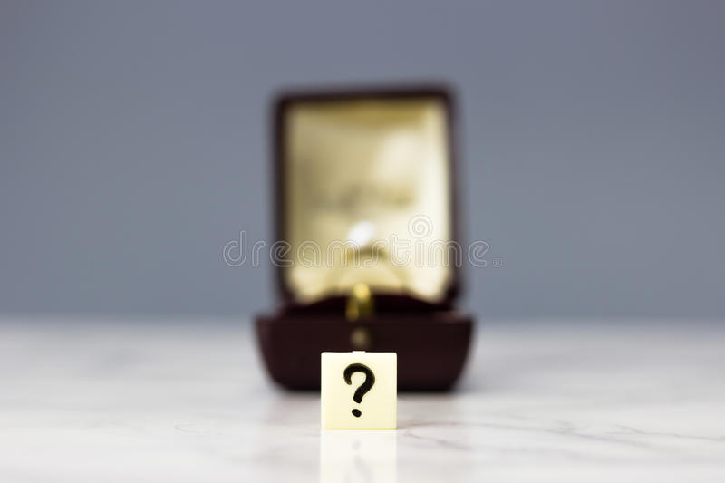 Engagement ring with question mark. On dark background royalty free stock photo