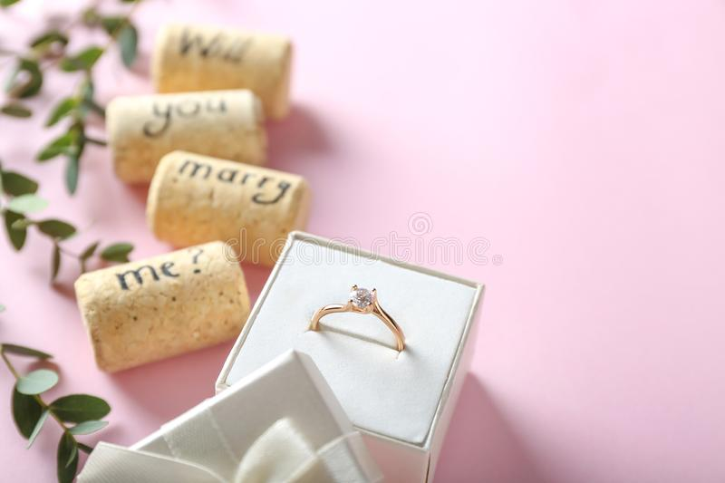 Engagement ring and text WILL YOU MARRY ME? on color background stock photos