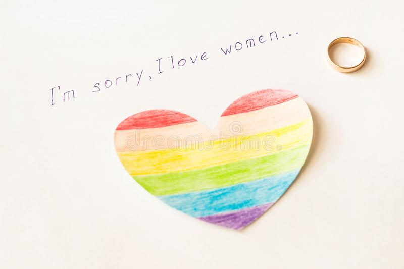Engagement ring on a white background and the inscription I love women, heart in the form of a LGBT flag, lesbian. Engagement ring on a white background and the stock photography