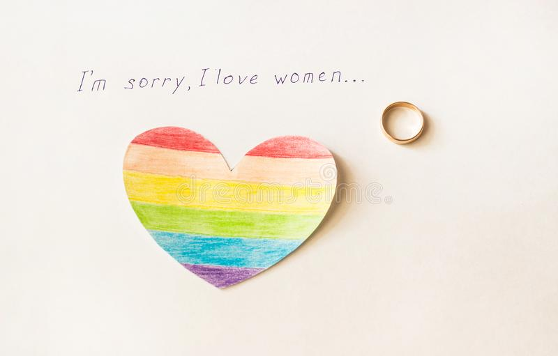 Engagement ring on a white background and the inscription I love women, heart in the form of a LGBT flag, lesbian. Engagement ring on a white background and the stock photo