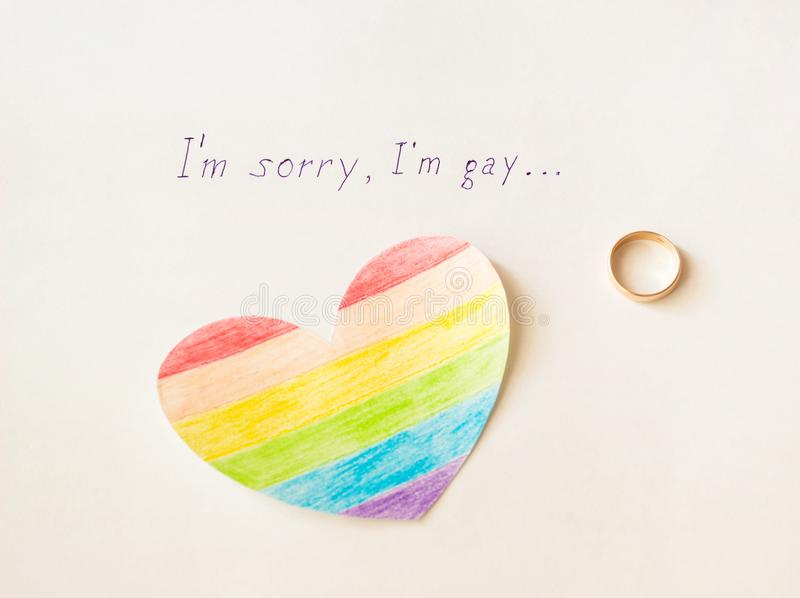 Engagement ring on a white background and an inscription, I`m sorry gay, heart in the form of a LGBT flag, homosexuality, love. Engagement ring on a white royalty free stock photo