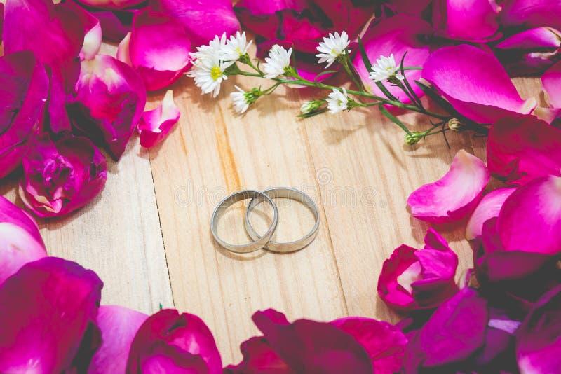 Engagez l'anneau parmi le fond en bois dessus mis par rose de pétale image stock