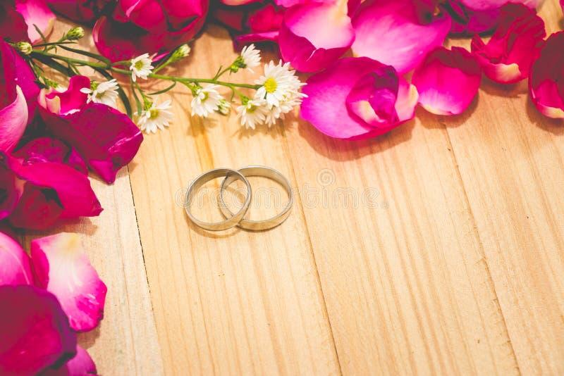 Engagez l'anneau parmi le fond en bois dessus mis par rose de pétale photographie stock