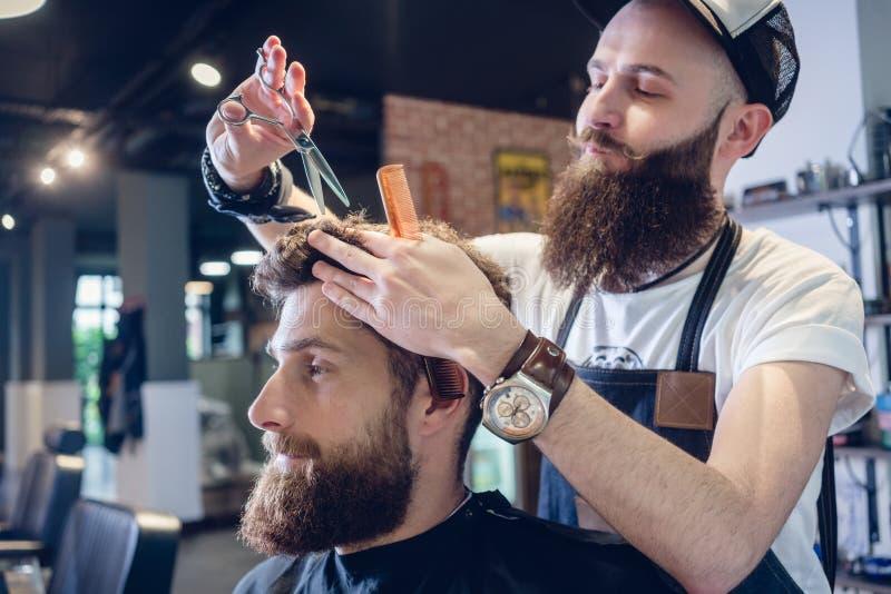 Engagierter Herrenfriseur, der Scheren und Kamm verwendet lizenzfreie stockbilder