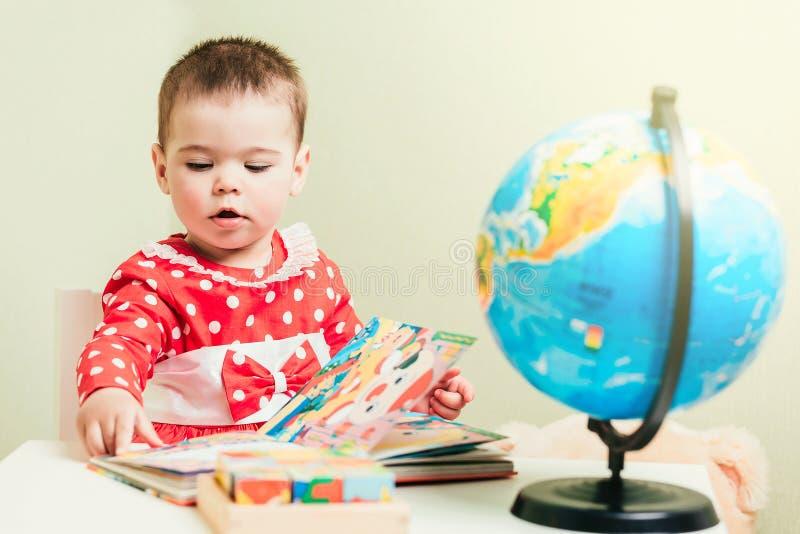 Engammal flicka i en röd klänning sitter på en tabell med en bok, ett jordklot och en nallebjörn arkivfoto