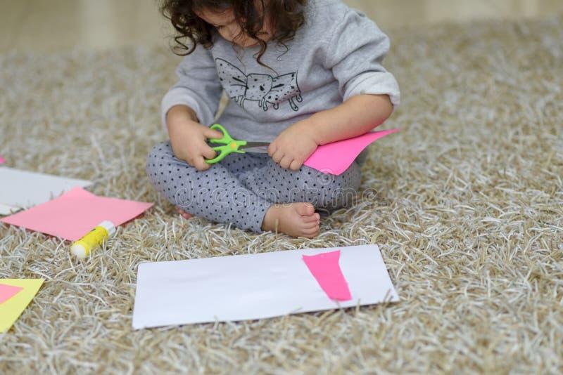 Engammal litet barnflicka klipper ut med sax, hantverk med barn arkivfoto
