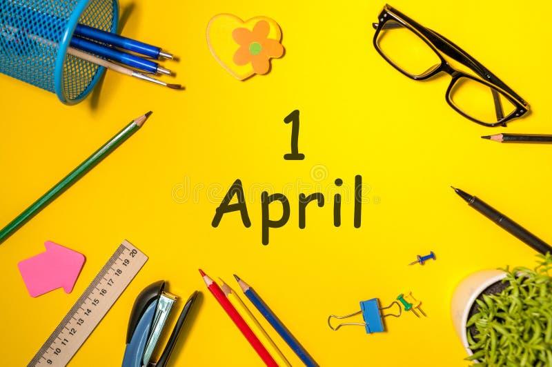 Engana o dia - 1º de abril dia 1 do mês de abril, calendário no fundo amarelo da mesa da escola O tempo de mola… aumentou as folh foto de stock royalty free