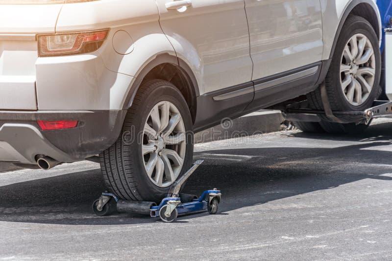Enganchado encima del coche en una grúa en un borde de la carretera, ciérrese encima de la vista de la rueda posterior de un coch fotografía de archivo libre de regalías