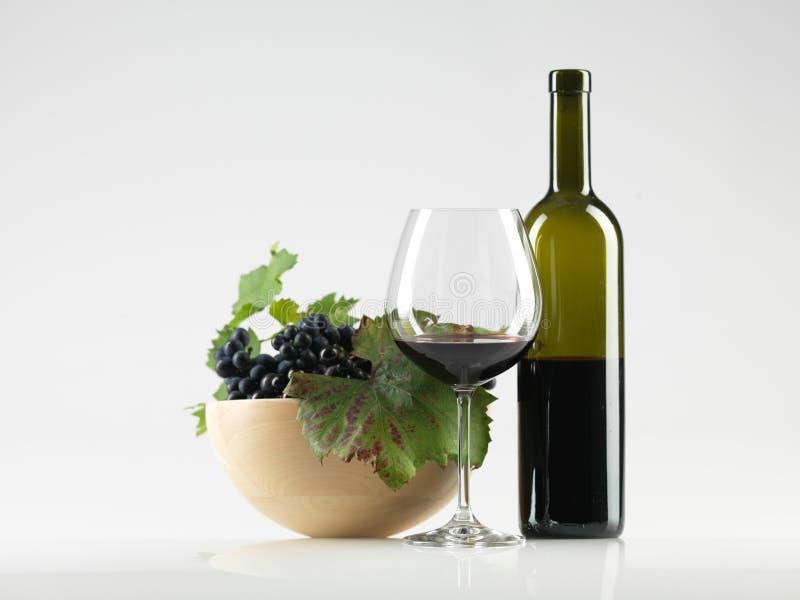 Engarrafe o vinho vermelho, vidro, fundo do branco das uvas fotografia de stock