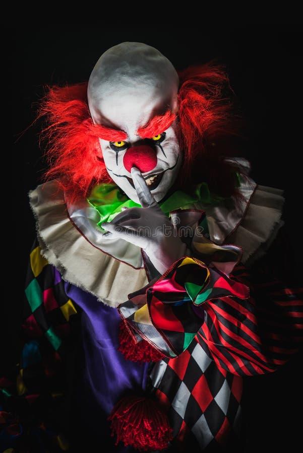 Enge clown op een donkere achtergrond royalty-vrije stock afbeeldingen