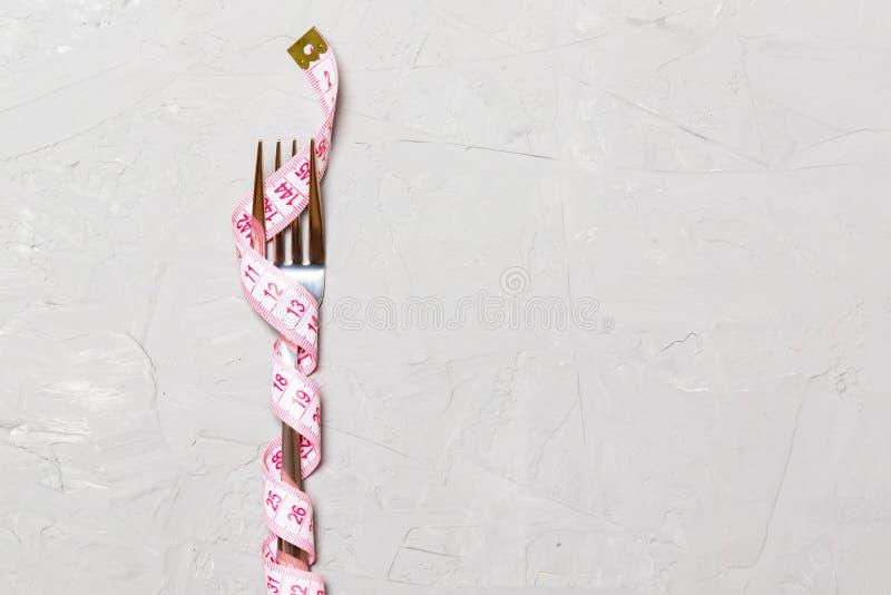 Enge Gabel mit Klebeband auf grauem Hintergrund Das Konzept der Fettleibigkeit lizenzfreie stockfotos