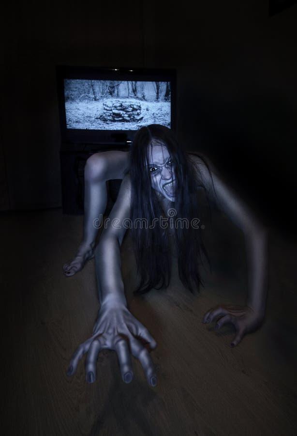 Enge Halloween-foto Het dode zombiemeisje beklimt uit de put F stock afbeelding