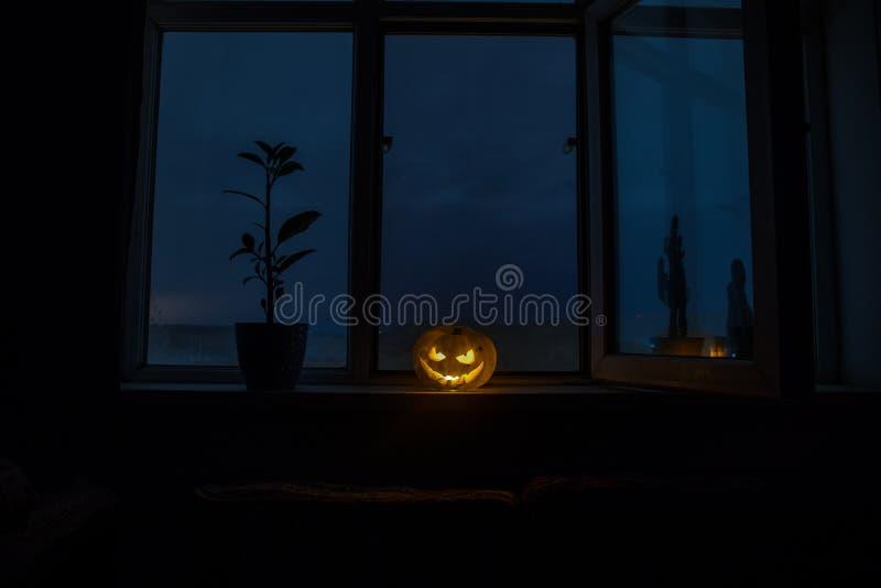 Enge Halloween-pompoen in het mystieke huisvenster bij nacht of Halloween-pompoen in nacht op ruimte met blauw venster Symbool va stock illustratie