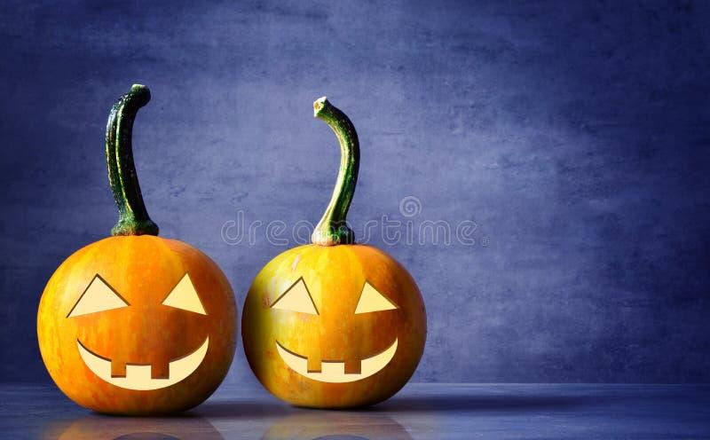Enge Halloween-pompoenen op een blauwe achtergrond De enge het glimlachen gezichtentruc of behandelt royalty-vrije stock fotografie