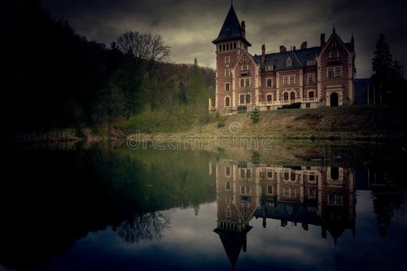 Enge mening van een kasteel met een meer en bezinning in het bos stock foto's