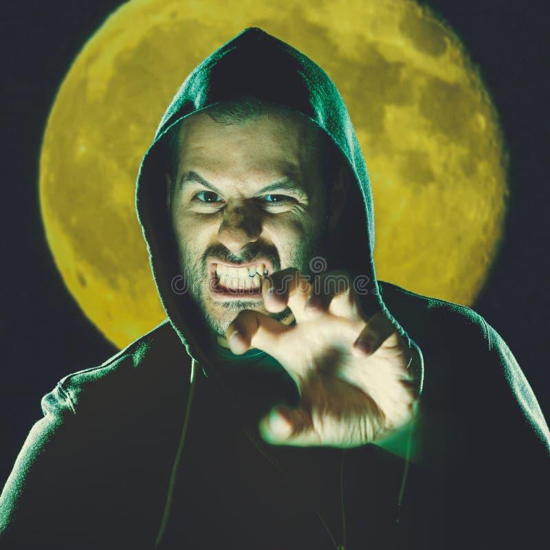 Enge mens vóór volle maan in een nachtscène stock afbeeldingen