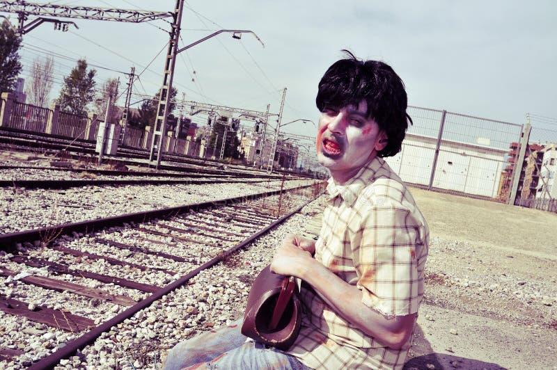 Enge zombiemens die op de trein wachten stock fotografie
