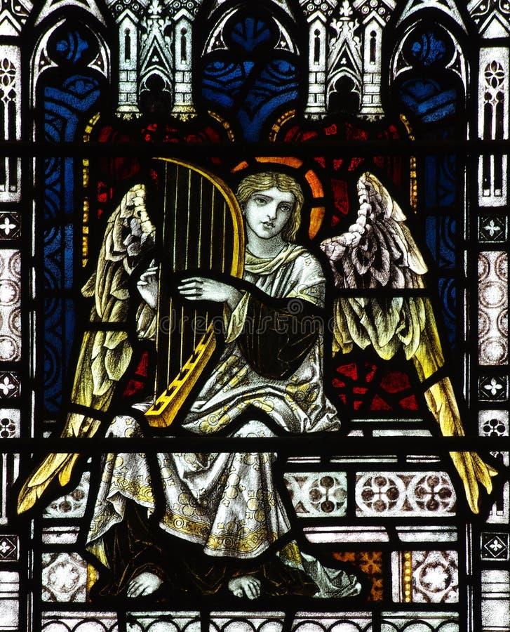 Engel, der Musik im Buntglas macht stockfotografie