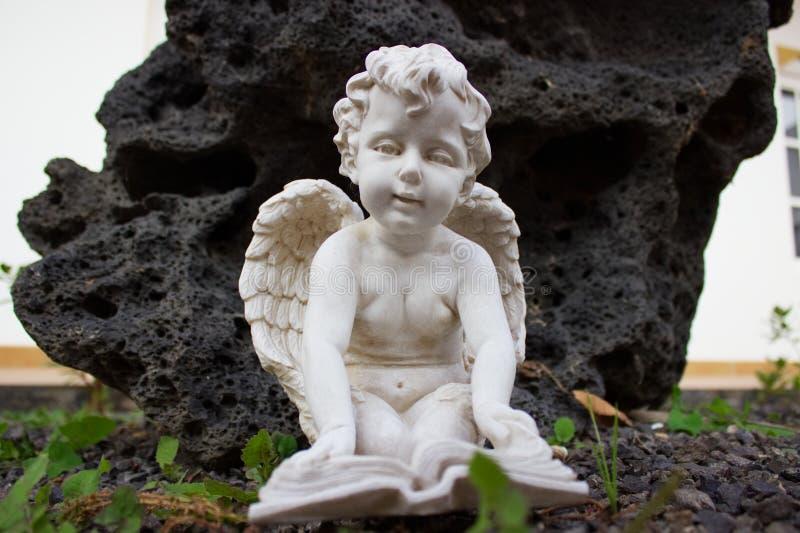 Engel die een boek op de vloer lezen stock fotografie
